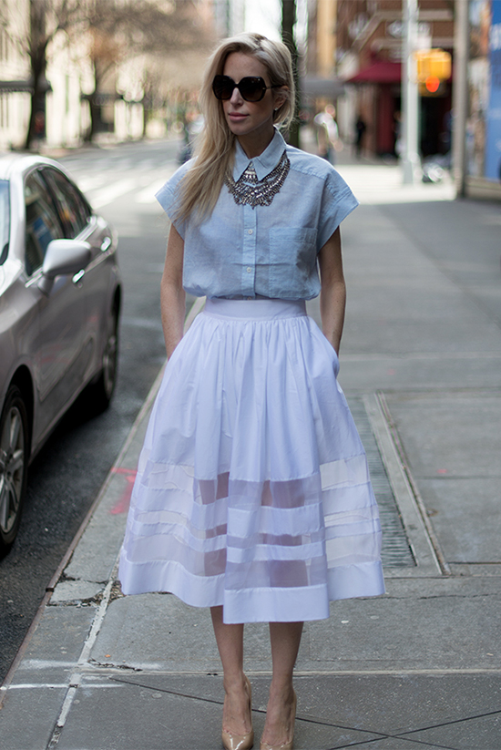 Street Style - The Top Blogger Looks Of The Week: Fashion blogger 'Yael Steren' wearing a pale blue boxy short sleeve shirt, a statement necklace, a white mesh panel midi skirt, nude heels and black sunglasses. Summer outfit, night out outfit, party outfit, street chic style.