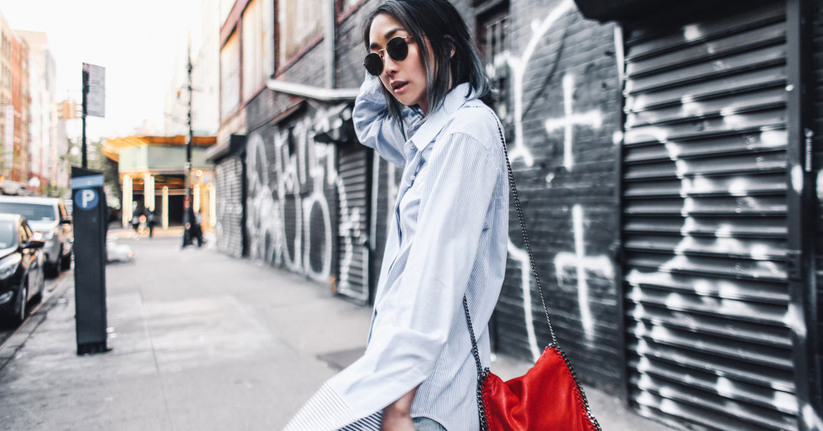 Spring outfit - A Cool Way To Wear The Extra-Long Sleeve Trend: Fashion Blogger 'The Spicy Stiletto' wearing a blue stripe extra-long sleeve shirt, light denim distressed boyfriend jeans, black and white heels, round aviator sunglasses and a red shoulder bag. Spring outfit, summer outfit, casual outfit, tomboy outfit.