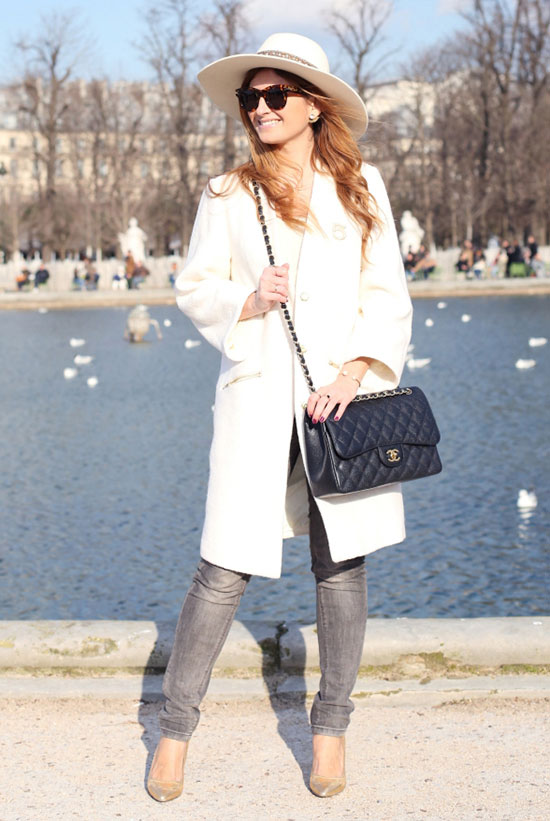 Street Style - The Top Blogger Looks Of The Week: Fashion blogger 'A Trendy Life' wearing a white wide brim hat, brown sunglasses, a white long blazer, a white top, grey skinny jeans, golden heels and a black shoulder bag. Spring outfit, casual outfit, street chic style.