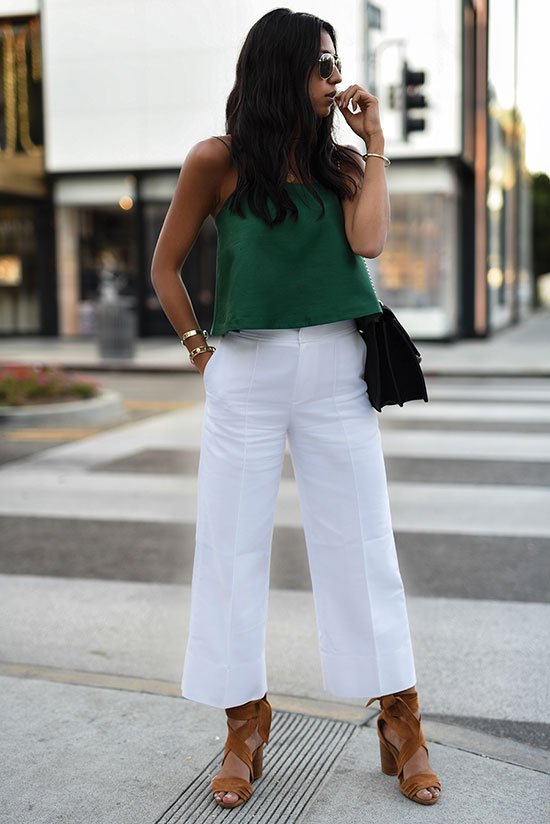 Street Style - The Top Blogger Looks Of The Week: Fashion blogger 'Not Your Standard' wearing a green sleeveless crop top, white culottes, brown suede lace-up sandals, aviator sunglasses and a black shoulder bag. Summer outfit, casual outfit, getaway outfit, party outfit, night out outfit.