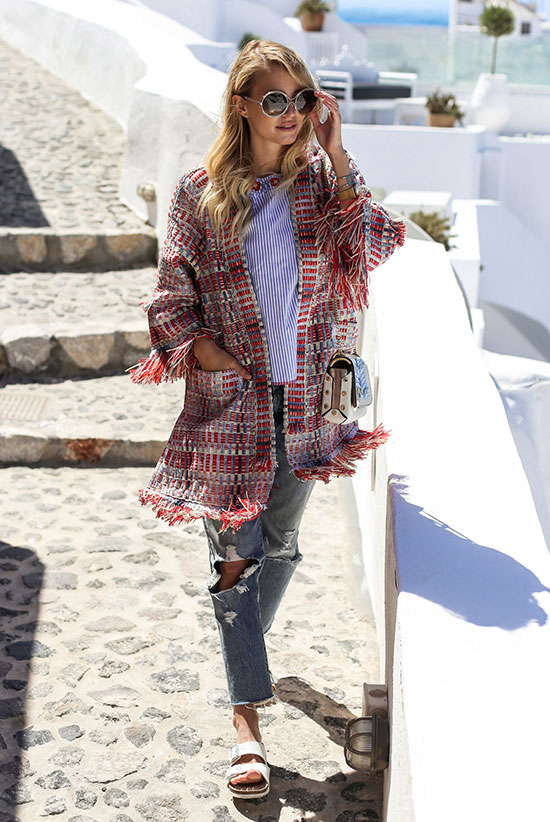 Street Style - The Top Blogger Looks Of The Week: Fashion blogger 'Ohh Couture' wearing a red tweed fringe jacket, a blue stripe top, distressed crop jeans, white birkenstock sandals, round sunglasses and a white shoulder bag. Summer outfit, spring outfit, comfy outfit, casual outfit, beach outfit, travel outfit, getaway outfit, vacation outfit.