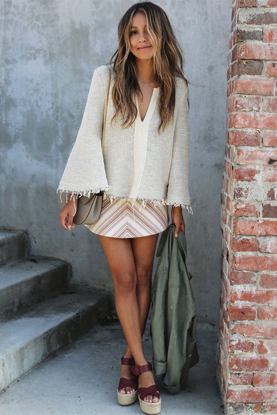Street Style - The Top Blogger Looks Of The Week: Fashion blogger 'Sincerely Jules' wearing a beige v-neck bell sleeve knit top, a stripe mini skirt, burgundy flatform sandals, a military utility jacket and a grey shoulder bag. Summer outfit, casual outfit, beach outfit, vacation outfit, getaway outfit, boho chic outfit, boho outfit, boho chic style.