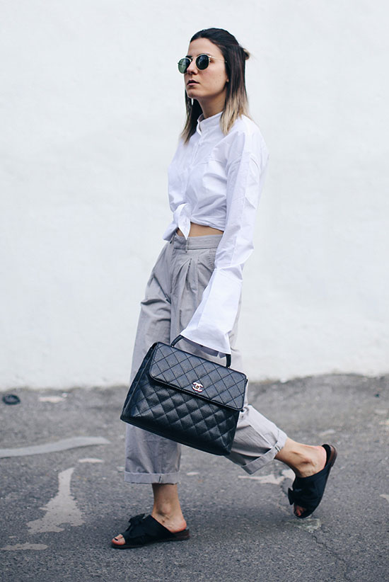 Summer outfits - The Top Blogger Looks Of The Week: Fashion blogger 'The Fashion Medley' wearing a white extra-long sleeve shirt, grey cuffed wide leg pants, black slide sandals, round aviator sunglasses and a black handbag. Summer outfit, comfy outfit, casual outfit, minimal outfit, street style.