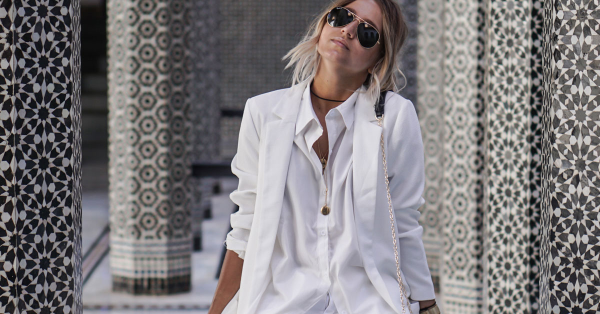 Summer Outfits - The Top Blogger Looks Of The Week: Fashion blogger 'Noholita wearing a white blazer, a white oversized shirt, white distressed denim shorts, white converse sneakers, aviator sunglasses and a black shoulder bag. Spring outfit, summer outfit, casual outfit, comfy outfit, sneakers outfit, athleisure outfit, all white outfit, travel outfit, getaway outfit, vacation outfit, casual outfit, street style.
