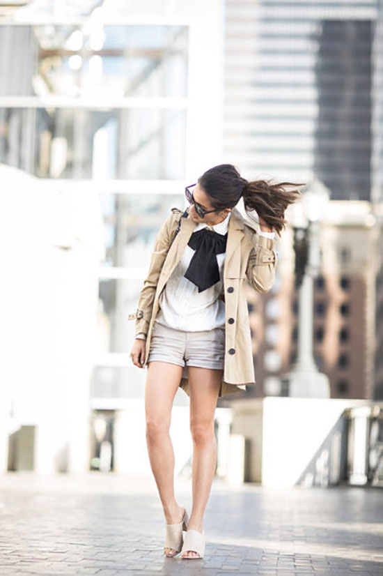 Summer Outfits - The Top Blogger Looks Of The Week: Fashion blogger 'Wendy's Lookbook' wearing a beige trench coat, a white shirt, a black oversized bow tie, khaki shorts, nude mule sandals and black sunglasses. Spring outfit, summer outfit, casual outfit, trench coat outfit, street style, street chic style.