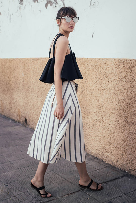 Summer Outfits - The Top Blogger Looks Of The Week: Fashion blogger 'Polienne' wearing a black ruffle crop top, a stripe midi skirt, black sandals and grey mirror sunglasses. Summer outfit, casual outfit, comfy outfit, beach outfit, summer getaway outfit, summer vacation outfit, street style.