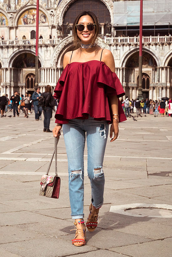 The Top Blogger Looks Of The Week: Fashion blogger 'Song of Style' wearing a burgundy ruffle off the shoulder top, distressed skinny jeans, red lace up sandals, round sunglasses and a burgundy suede handbag. Summer outfit, casual outfit, comfy outfit, summer getaway outfit, summer travel outfit, summer trends 2016, street style, street chic style.