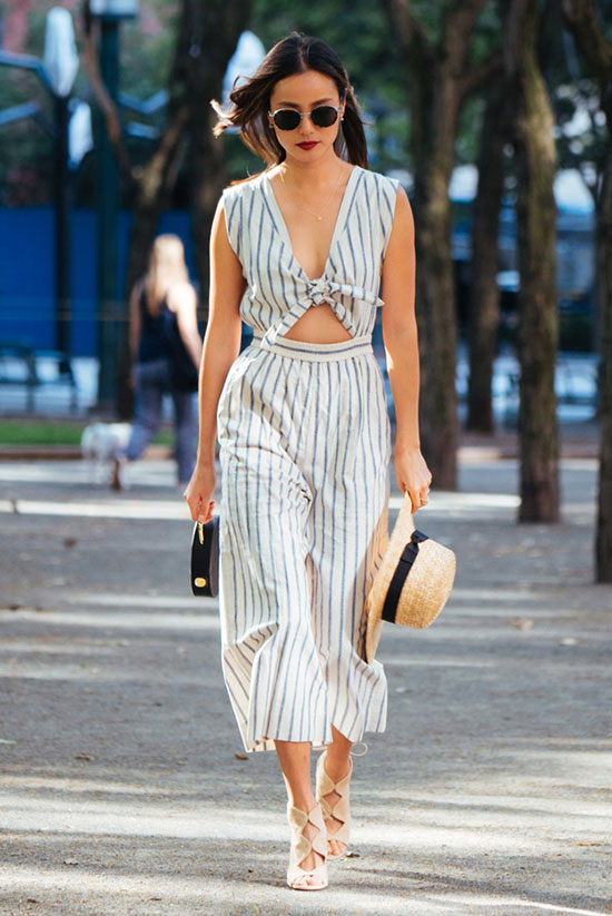 The Top Blogger Looks Of The Week: Fashion blogger 'What The Chung' wearing a stripe cutout jumpsuit, a straw boater hat, nude caged sandals, round sunglasses and a black handbag. Summer outfit, party outfit, street chic style, night out outfit, street style.