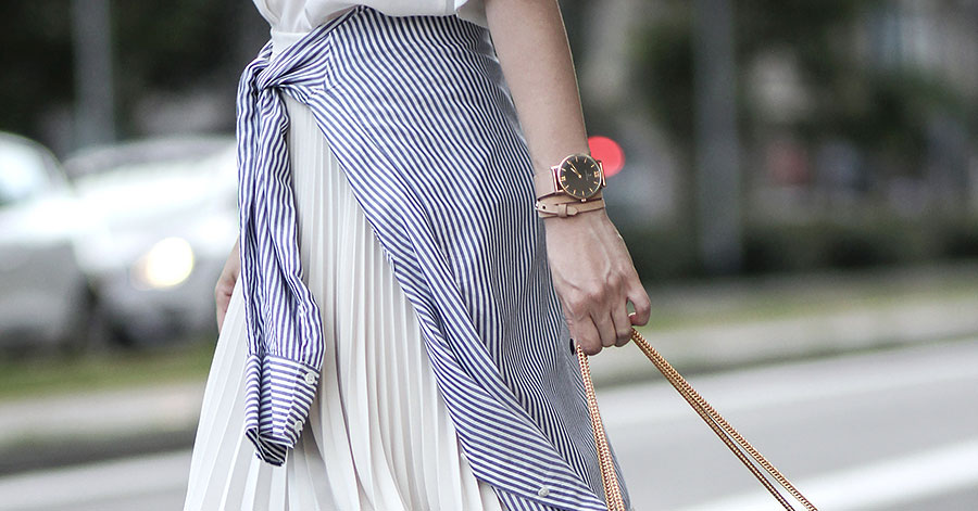 Simple Casual Trick: A Shirt Around The Waist - Fashion blogger 'Fake Leather' wearing a white silk shirt, a blue stripe shirt around the waist, a white pleated midi skirt, block heel sandals and a black shoulder bag. Summer outfit, spring outfit, summer work outfit, spring work outfit, casual outfit, street style, street chic style, shirt around the waist outfit.