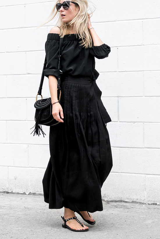 The Best Outfit Ideas Of The Week - Fashion blogger 'Figtny' wearing a black off the hsoulder top, a black maxi skirt, black studded sandals, black sunglasses and a black shoulder bag. Spring outfit, summer outfit, casual outfit, comfy outfit, all black outfit, beach outfit, summer travel outfit, summer getaway outfit, summer vacation outfit, night out outfit, minimal outfit.