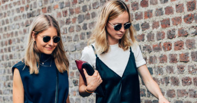 How To Wear The Slip Dress Over T-shirt Trend: Model wearing a black silk v-neck slip dress over a white t-shirt, black suede wedges, round sunglasses and a color-block clutch. Spring outfit, summer outfit, black & white outfit, spring trends 2016, casual outfit, summer trends 2016, street style, street chic style.