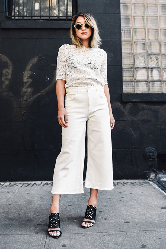 Summer Outfits - The Top Blogger Looks Of The Week: Fashion blogger 'The Spicy Stiletto' wearing a white lace top, white culottes, black mule sandals and round sunglasses. Summer outfit, black and white outfit, casual outfit, all white outfit, night out outfit, street style, street chic style.
