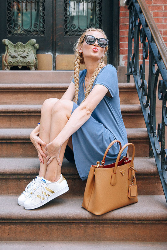 The Best Outfit Ideas Of The Week: Fashion blogger 'Barefoot Blonde' wearing a blue knit dress, white sneakers, black round sunglasses and a brown tote bag. Summer outfit, athleisure outfit, casual outift, comfy outfit, sneakers outfit, street style, street chic style, summer travel outfit, summer vacation outfit.