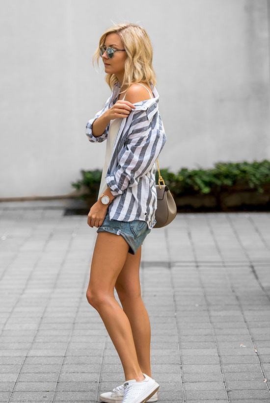The Best Outfit Ideas Of The Week: Fashion blogger 'The Rue Collective' wearing a blue stripe shirt, a white cami top, distressed denim shorts, white sneakers, silver mirror sunglasses and a grey shoulder bag. Summer outfit, spring outfit, comfy outfit, casual outfit, athleisure outfit, street style, beach outfit, summer travel outfit, summer vacation outfit.