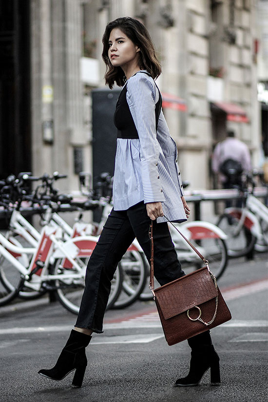 The Best Outfit Ideas Of The Week: Fashion blogger 'Fake Leather' wearing a blue stripe tunic shirt, black crop jeans, black mid-calf booties, a black crop vest and a brown shoulder bag. Spring outfit, fall outfit, work outfit, office wear, edgy outfit, fall trends 2016, street style, street chic style.