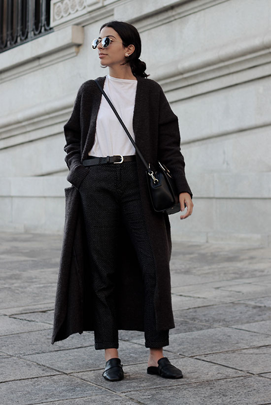 The Best Outfit Ideas Of The Week: Fashion blogger 'Fashion Mask' wearing a black long cardigan, a white t-shirt, a black belt, dark grey ankle pants, black flat mules, round sunglasses and a black shoulder bag. Spring outfit, fall outfit, black and white outfit, casual outfit, work outfit, office outfit, comfy outfit, fall layers, minimal outfit, street style, cardigan outfit, easy outfit, simple outfit.