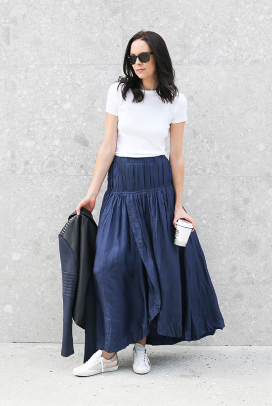 5 Casual Takes On The Pleated Skirt: Fashion blogger 'Fifi Deluxe' wearing a white t-shirt, a blue pleated maxi skirt, white sneakers, black sunglasses and a black leather jacket. Spring outfit, summer outfit, fall outfit, casual outfit, sneakers outfit, comfy outfit, minimal outfit, edgy outfit, maxi skirt outfit, metallic skirt outfit, pleated skirt outfit, street style, street chic style, fall trends 2016.