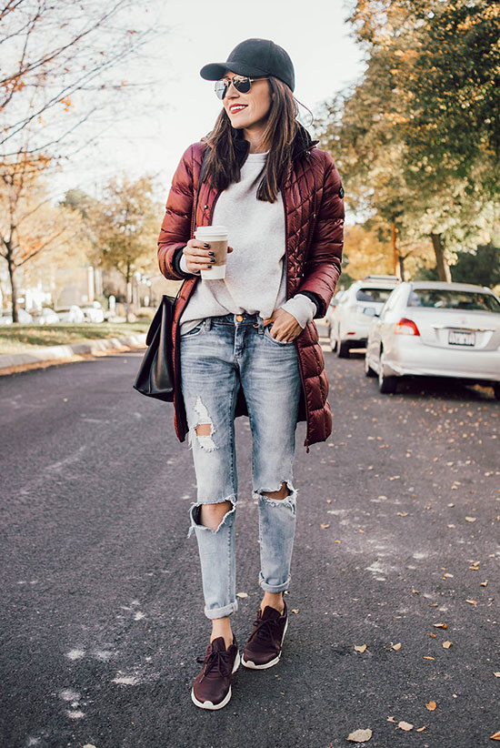 The Best Outfit Ideas Of The Week: Fashion blogger 'Hello Fashion Blog' wearing a black baseball cap, a burgundy puffer jacket, a grey sweatshirt, light distressed boyfriend jeans, burgundy sneakers, a black shoulder bag and aviator sunglasses. Street style, casual outfit, comfy outfit, weekend outfit, game day outfit, travel outfit, athleisure outfit, Sunday outfit, sneakers outfit.