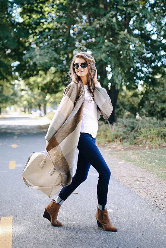 The Best Outfit Ideas Of The Week: Fashion blogger 'Southern Curls & Pearls' wearing a brown checkered cape, a white long sleeve t-shirt, solid skinny jeans, brown wedge booties, black sunglasses and a white handbag. Fall outfit, casual outfit, night out outfit, travel outfit, comfy outfit, street chic style, street style.