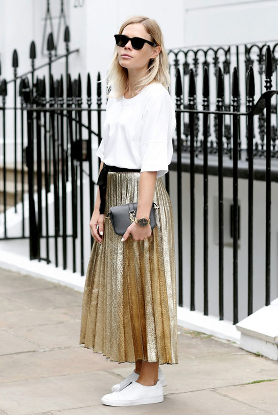 5 Casual Takes On The Pleated Skirt: Fashion blogger 'We The People' wearing a white t-shirt, a golden pleated midi skirt, white sneakers, black sunglasses and a black shoulder bag. Street style, pleated skirt outfit, pleated skirt casual outfit, sneakers outfit, spring outfit, summer outfit, fall outfit, casual outfit, street chic style, summer trends 2016, fall trends 2016.