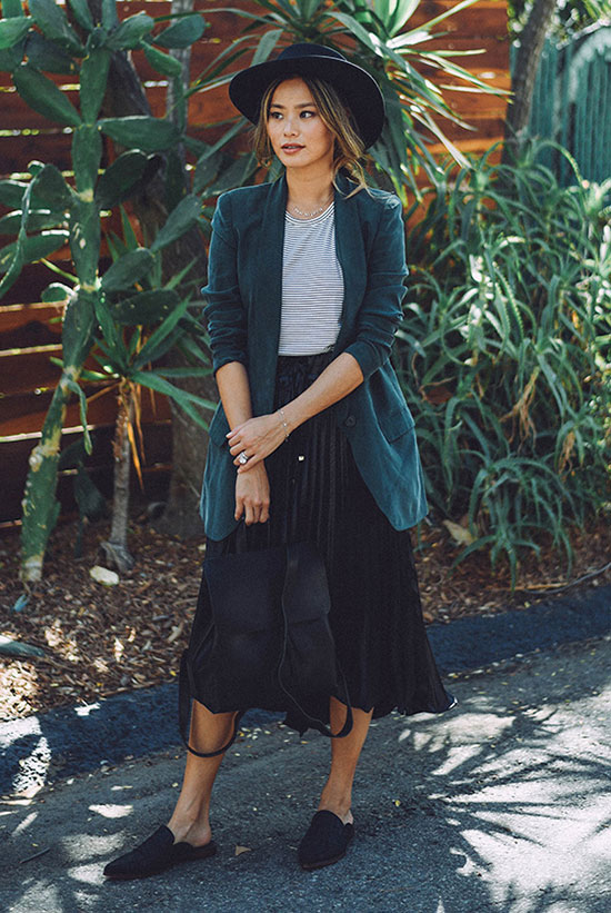 The Best Outfit Ideas Of The Week: Fashion blogger 'What The Chung' wearing a black fedora, a green blazer, a grey t-shirt, a black pleated midi skirt, black flat mules and a black suede backpack. Spring outfit, fall outfit, work outfit, office wear, office outfit, casual outfit, comfy outfit, night out outfit, street style, fall layers.