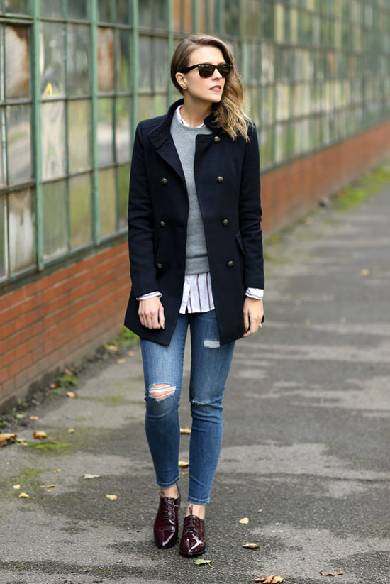 The Best Outfit Ideas Of The Week: Fashion blogger 'Penny Pincher Fashion' wearing a navy military coat, a grey sweater, a stripe shirt, distressed skinny jeans, burgundy oxfords and black sunglasses. Fall outfit, winter outfit, fall layers, winter layers, comfy outfit, casual outfit, travel outfit, street style.