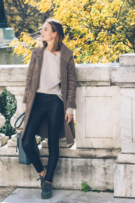 The Best Outfit Ideas Of The Week: Fashion blogger 'Prosecco & Plaid' wearing a brown shearling jacket, a cream sweater, black leather pants and black sneakers. Winter outfit, casual outfit, travel outfit, comfy outfit, winter layers, street style.