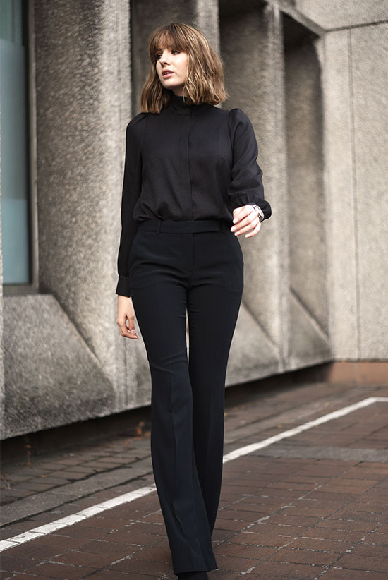 The Best Outfit Ideas Of The Week: Fashion blogger 'Shot From The Street' wearing a black mock neck blouse, black flare pants and black suede booties. Fall outfit, all black outfit, easy outfit, work outfit, office outfit, business casual, simple outfit, office style, street style, street chic style.