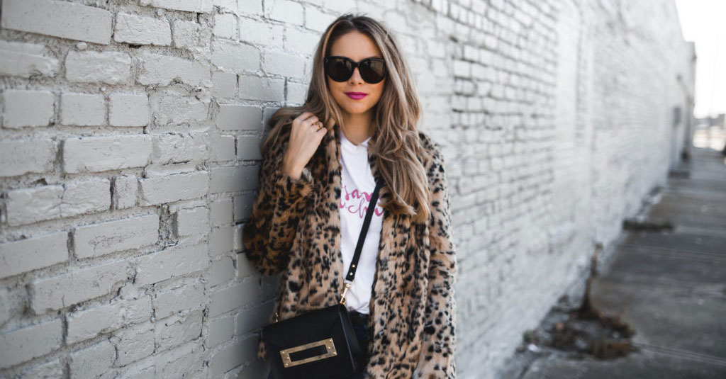 10 Cool Ways To Wear A Leopard Coat This Winter: Fashion blogger 'The Teacher Diva' wearing a leopard coat, a white graphic t-shirt, distressed skinny jeans, a black belt, white studded flats, black cat eye sunglasses and a black shoulder bag. Fall outfits, winter outfits, leopard coat outfits, leopard print outfits, casual outfits, street style, comfy outfits, travel outfits, fashion trends 2017, winter fashion trends, winter fashion trends 2017
