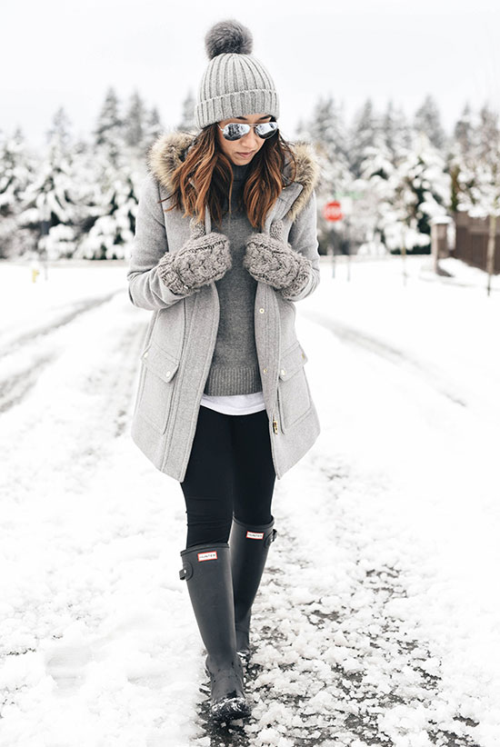 5 Stylish Snow Outfit Ideas: Fashion blogger 'Crystalin Marie' wearing a grey pom pom beanie, a grey hooded coat, mirror aviator sunglasses, a grey sweater, a white shirt, black leggings, grey knit gloves and a black rain boots. Casual outfit, snow outfit, snow day outfit, winter outfit, winter layers, rain day outfit, comfy outfit, skiing trip outfit, cold weather outfit, cozy outfit, monochromatic outfit, all grey outfit.