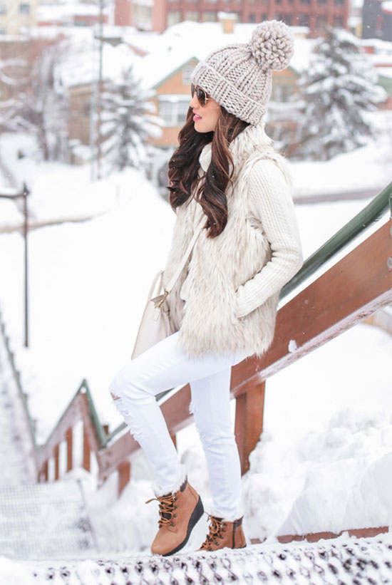 5 Stylish Snow Outfit Ideas: Fashion blogger 'Extra Petite' wearing a light grey pom pom beanie, aviator sunglasses, a beige turtleneck sweater, a white fur vest, white skinny jeans, brown snow boots and a white shoulder bag. Casual outfit, snow outfit, snow day outfit, winter outfit, rain day outfit, comfy outfit, skiing trip outfit, cold weather outfit, cozy outfit, neutral tone outfit, monochromatic outfit, all white outfit.