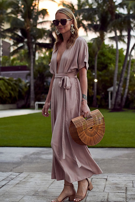 20 Cute Valentine's Day Outfits For Every Situation: Fashion blogger 'Fashion Jackson' wearing a pink maxi dress (pink short sleeve maxi dress), nude sandals, brown sunglasses and a basket bag. Street style, summer outfit, beach outfit, travel outfit, romantic outfit, date night outfit, party outfit, summer wedding outfit, valentine's day outfit.