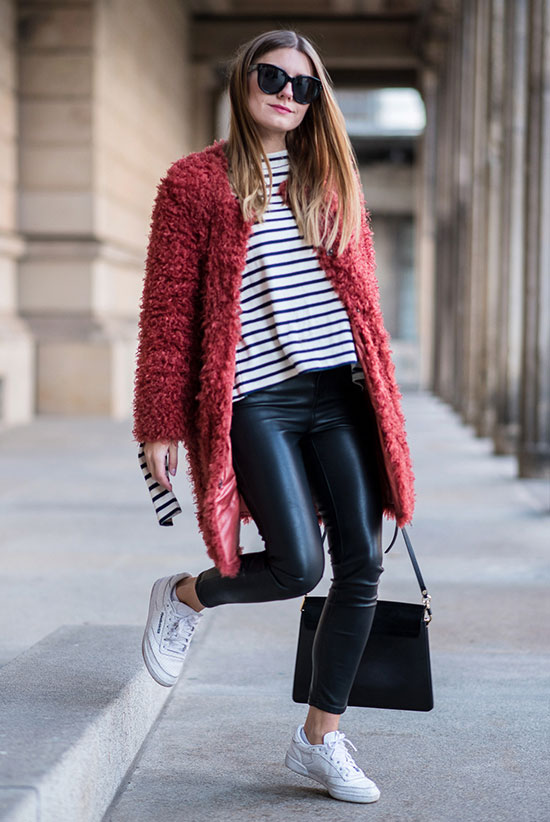 20 Cute Valentine's Day Outfits For Every Situation: Fashion blogger 'Hoard of Trends' wearing a red oversized cardigan, a stripe t-shirt, black leather leggings, white sneakers, black sunglasses and a black handbag. Street style, casual outfit, comfy outfit, fall outfit, athleisure outfit, valentine's day outfit, casual valentine's day outfit.