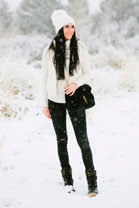 5 Stylish Snow Outfit Ideas: Fashion blogger 'Pink Peonies' wearing a white pom pom beanie, a white turtleneck sweater, a white puffer vest, black skinny jeans, black snow boots and a black shoulder bag. Casual outfit, snow outfit, snow day outfit, winter outfit, rain day outfit, comfy outfit, skiing trip outfit, cold weather outfit, cozy outfit, black and white outfit.