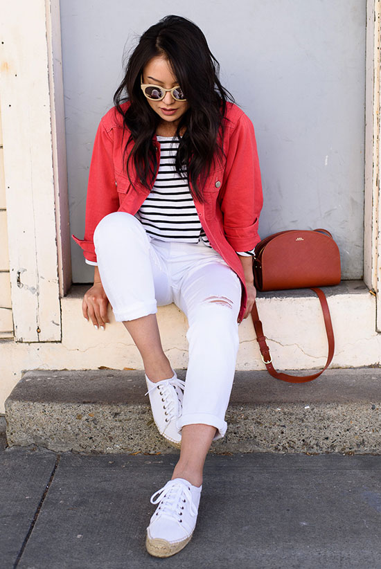 20 Cute Valentine's Day Outfits For Every Situation: Fashion blogger 'The Fancy Pants Report' wearing a red denim jacket, a stripe t-shirt, white boyfriend jeans, white espadrille sneakers, a red shoulder bag and pink round sunglasses. Spring outfit, summer outfit, casual outfit, comfy outfit, travel outfit, valentine's day outfit, street style.