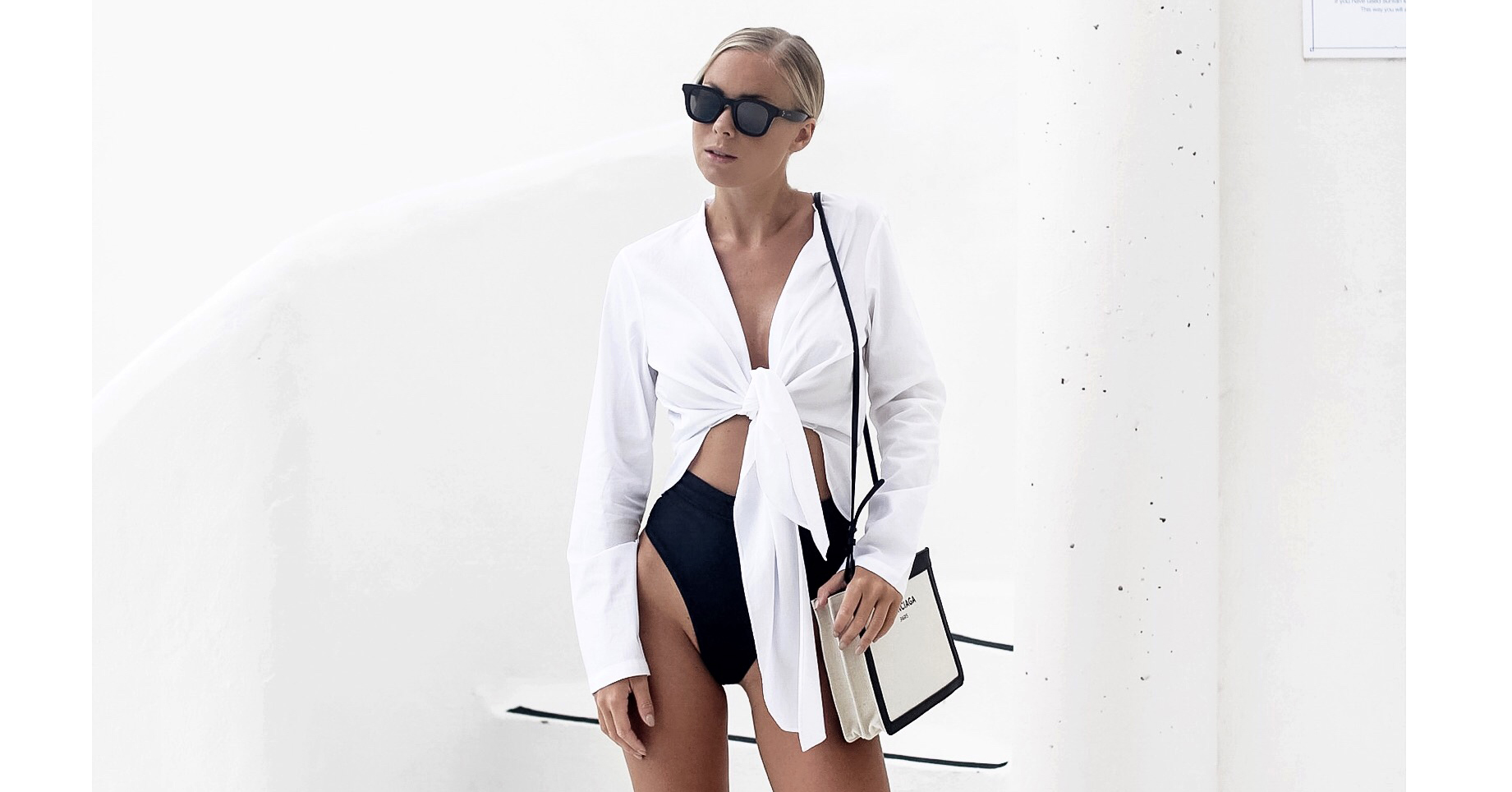 15 Casual-Chic Beach Outfits To Try This Swimsuit Season: Fashion blogger 'Victoria Tornegren' wearing a white tie front crop shirt, a black cutout swimsuit, black slide sandals, a colorblock shoulder bag and black square sunglasses. Beach outfit, pool outfit, summer outfit, vacation outfit, getaway outfit, swimsuit outfit, swimwear outfit, summer fashion trends, summer fashion trends 2017, swimwear trends 2017.