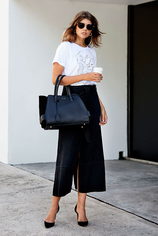 20+ Fresh & Chic Summer Work Outfits: Fashion blogger 'Badlands' wearing a white graphic t-shirt, a black belted midi skirt, black d'orsay pumps, black rounded sunglasses and a black structured handbag. Work outfits, summer work outfits, outfits for work, office outfits, office wear, simple work outfits, work outfits 2017, minimal outfits, black and white outfits, monochrome outfits.