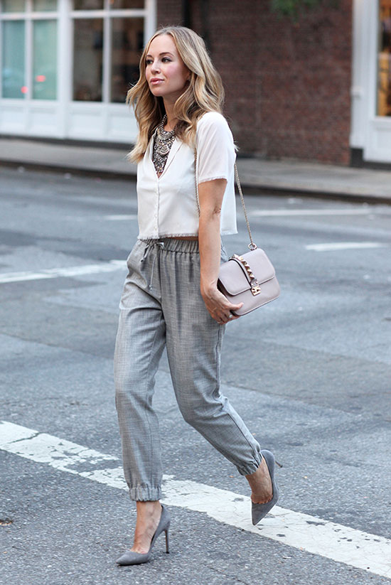 20+ Fresh & Chic Summer Work Outfits: Fashion blogger 'Brooklyn Blonde' wearing a white short sleeve crop top, grey crop pants, grey suede heels, a statement necklace and a beige shoulder bag. Work outfits, summer work outfits, outfits for work, office outfits, office wear, simple work outfits, work outfits 2017, fresh work outfits, neutral tone outfits.