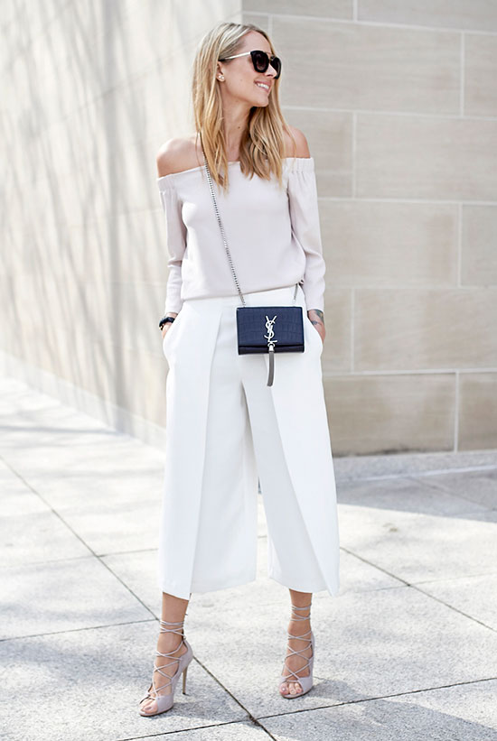 20+ Fresh & Chic Summer Work Outfits: Fashion blogger 'Fashion Jackson' wearing an ivory off the shoulder top, white wide leg crop pants, beige lace up heels, black sunglasses and a black shoulder bag. Work outfits, summer work outfits, outfits for work, office outfits, office wear, simple work outfits, work outfits 2017, fresh work outfits, spring work outfits, neutral tone outfits, all white outfits.