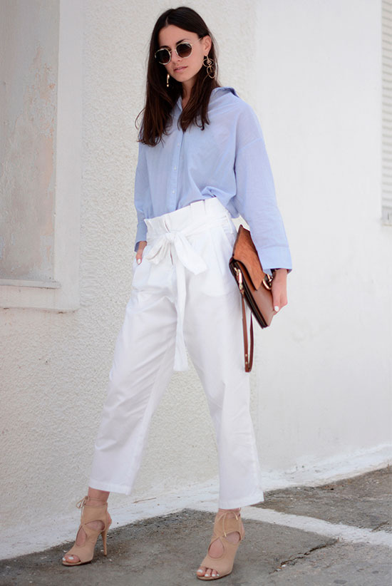 20+ Fresh & Chic Summer Work Outfits: Fashion blogger 'Fashion Vibe' wearing a pale blue oversized shirt, white paperbag pants, nude lace-up heels, a brown shoulder bag and rounded aviator sunglasses. Work outfits, summer work outfits, outfits for work, office outfits, office wear, simple work outfits, work outfits 2017, minimal outfits, fresh work outfits.