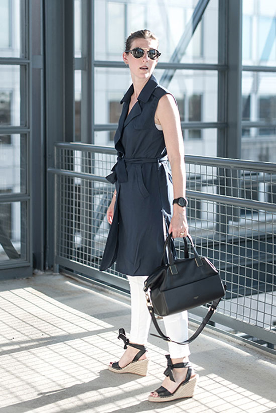 20+ Fresh & Chic Summer Work Outfits: Fashion blogger 'Meg Biram' wearing a navy sleeveless trench coat, a white tank top, white skinny jeans, navy espadrille wedges, black round sunglasses and a black handbag. Work outfits, summer work outfits, outfits for work, office outfits, office wear, simple work outfits, work outfits 2017, comfy work outfits, vacation outfits.