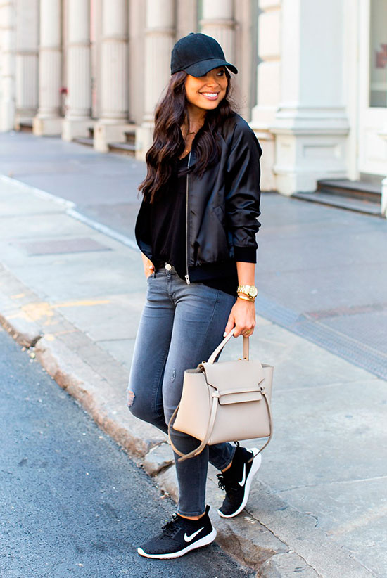 5 Ultra Comfy Sneakers Outfits Perfect For Fall: Fashion blogger 'With Love From Kat' wearing a black baseball cap, a black bomber jacket, a black t-shirt, grey skinny jeans, black sneakers and a beige handbag. Fall outfits, comfy outfits, sneakers outfits, athleisure, athleisure outfits, weekend outfits, back to school outfits, casual outfits, travel outfits, nike juvenate sneakers, nike juvenate outfits, black sneakers outfits.