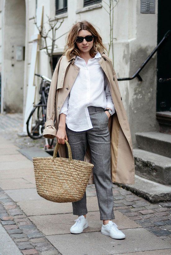 40 Ultra-Chic Fall Outfits To Try Right Now: Fashion blogger 'Brittany Bathgate' wearing a beige trench coat, a white shirt, grey ankle pants, white canvas sneakers, black sunglasses and a straw tote. Fall outfits, fall fashion trends 2017, fall fashion, street style, casual outfits, trench coat outfits, work outfits, office outfits, travel outfits.