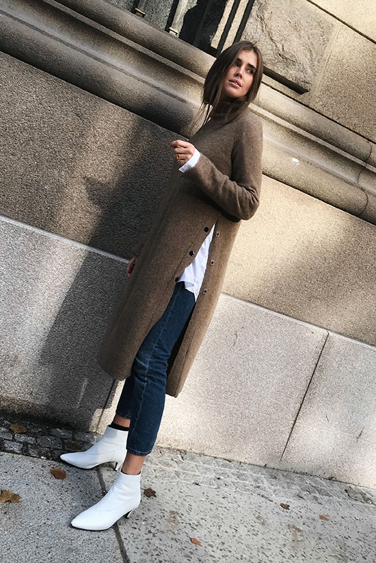 40 Ultra-Chic Fall Outfits To Try Right Now: Fashion blogger 'Darja Barannik' wearing a brown slit sweater tunic, a white long sleeve blouse, crop skinny jeans and white booties. Fall outfits, fall fashion trends 2017, fall fashion, street style, casual outfits, fall layers.