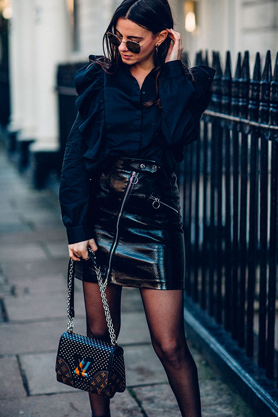 40 Ultra-Chic Fall Outfits To Try Right Now: Fashion blogger 'Fashion Vibe' wearing a black ruffle sleeve shirt, a black PU mini skirt, black tights, black booties, round aviator sunglasses and a black studded chain strap bag. Fall outfits, fall fashion trends 2017, fall fashion, street style, party outfits, night out outfits, all black outfits, mini skirt outfits, trendy outfits, chic outfits.