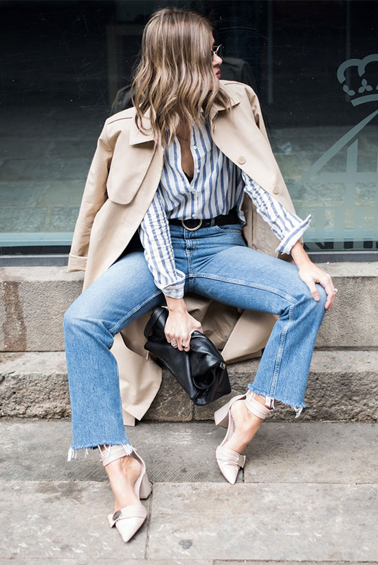 40 Ultra-Chic Fall Outfits To Try Right Now: Fashion blogger 'Ms Treinta' wearing a beige trench coat, a blue stripe shirt, raw hem straight jeans, beige bow heels and a black shoulder bag. Fall outfits, fall fashion trends 2017, fall fashion, street style, chic outfits, work outfits, office outfits, dinner outfits, trench coat outfits.