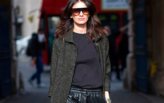 15 It Girl Approved Winter Work Outfits: Leila Yavari wearing a dark grey coat, a black t-shirt, black leather ankle pants, black heels and two tone sunglasses.