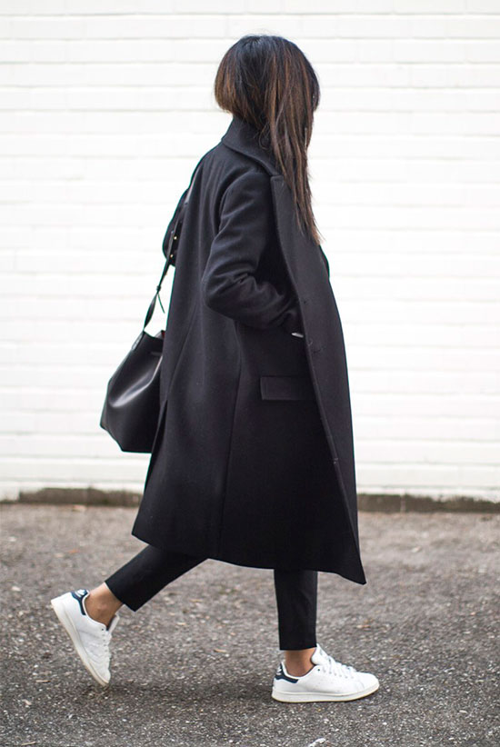 10 Simple Ways To Style A Long Coat: Fashion blogger 'Fashion Landscape' wearing a black long coat, a white shirt, black ankle pants, white sneakers, black sunglasses and a black bucket bag.