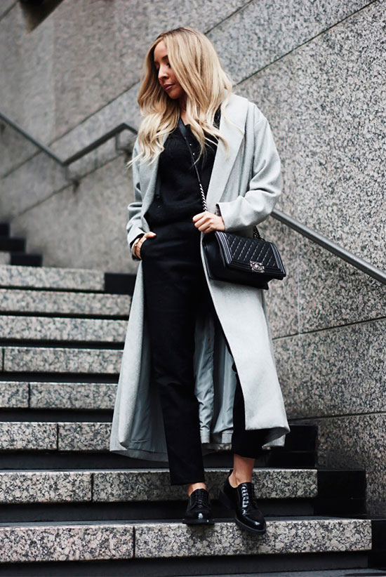 10 Simple Ways To Style A Long Coat: Fashion blogger 'Haute Instinct' wearing a grey long coat, a black sweater, black ankle pants, black oxfords and a black quilted bag.