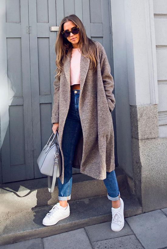 10 Simple Ways To Style A Long Coat: Fashion blogger 'Kenza' wearing a taupe long coat, a white crop t-shirt, mom jeans, white sneakers, brown sunglasses and a grey handbag.